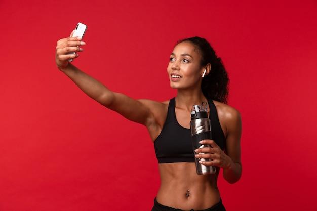 Imagen de una hermosa joven africana deportes fitness mujer posando aislada sobre pared roja escuchando música con auriculares tomar un selfie por teléfono móvil sosteniendo una botella con agua.