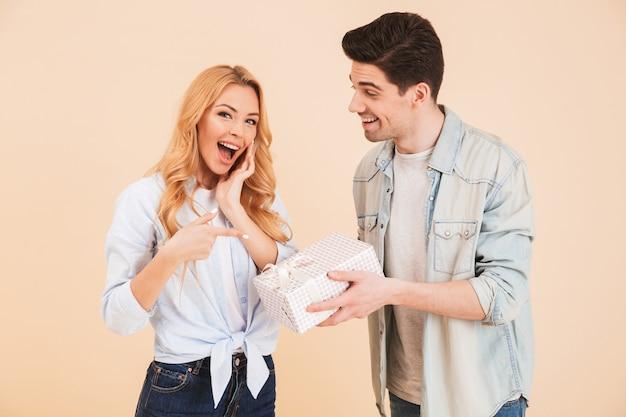 Imagen de la hermosa joven apuntando con el dedo a la caja de cumpleaños sosteniendo por un atractivo hombre morena, aislado sobre pared beige