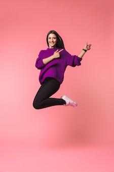 Imagen de una hermosa joven emocional posando aislada sobre espacio rosa mostrando copyspace saltando.