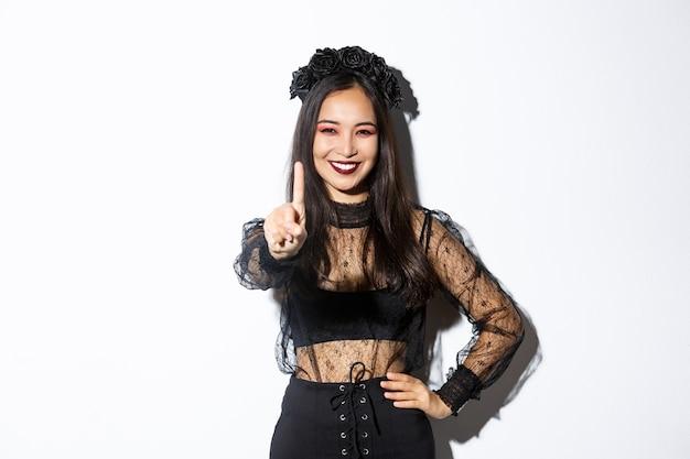 Imagen de una hermosa mujer asiática sonriente en traje de halloween que muestra un gesto de parada, extiende un dedo y parece feliz, prohíbe o rechaza algo, fondo blanco de pie.