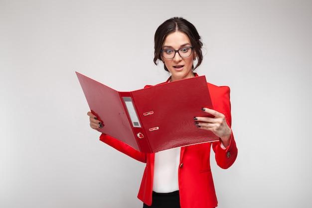 Imagen de hermosa mujer en blazer rojo de pie con documentos en manos