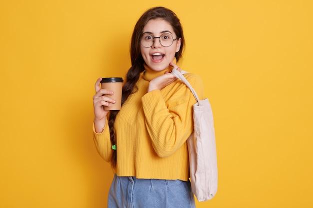 Imagen de hermosa mujer elegante con bolsa ecológica y café para llevar, dama con expresión facial emocionada, vistiendo ropa casual y gafas.