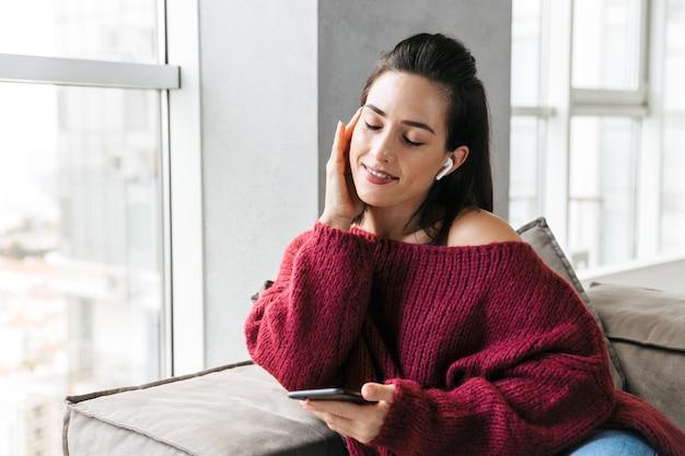 Imagen de una hermosa mujer en el interior de su casa en el sofá con teléfono móvil escuchando música con auriculares.
