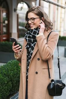 Imagen de una hermosa mujer joven al aire libre caminando por la calle con teléfono móvil escuchando música con auriculares.
