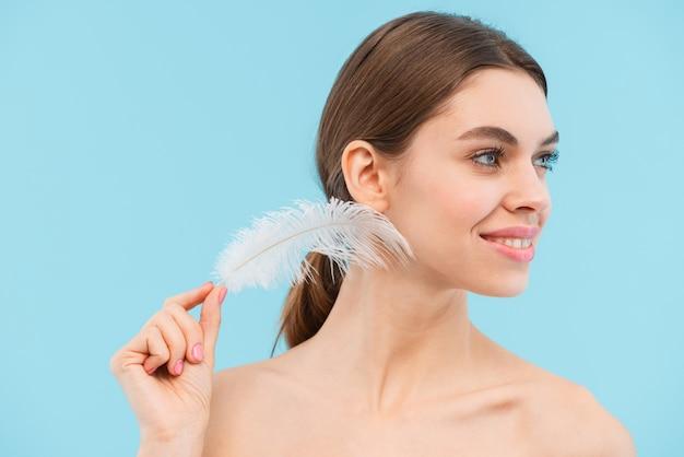Imagen de hermosa mujer joven feliz posando aislado sosteniendo la pluma.