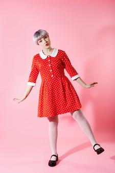 Imagen de una hermosa niña dollish con cabello corto violeta claro con un vestido rojo sobre una pared rosa