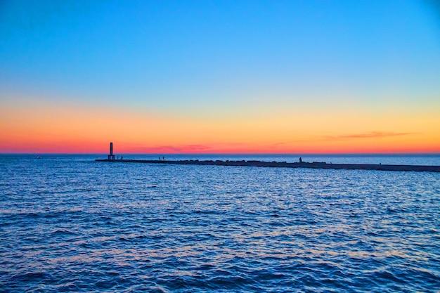 Imagen de hermoso atardecer o amanecer en el lago con silueta de muelle y cielo colorido de rojo, naranja y azul