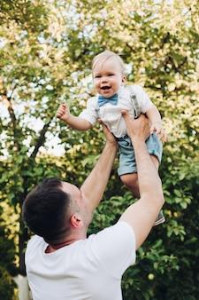 Imagen de hermoso papá caucásico sostiene a su pequeño y bonito hijo en las manos y se regocijan juntos afuera en verano