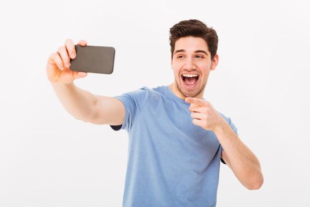 Imagen del hombre 30s con cabello castaño sonriendo y señalando con el dedo a la cámara mientras toma selfie en teléfono celular negro, aislado sobre la pared blanca