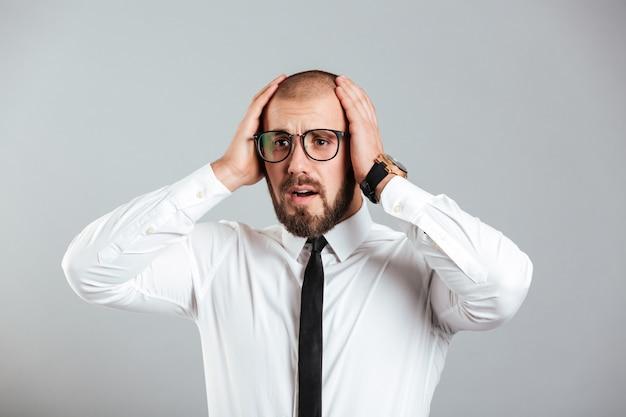 Imagen de un hombre adulto de 30 años con camisa blanca y anteojos agarrando su cabeza expresando su problema o falla, aislado sobre la pared gris