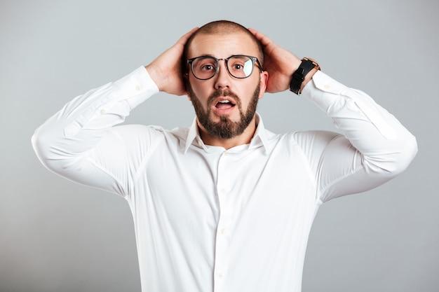 Imagen de hombre adulto confundido o sorprendido con camisa blanca y anteojos agarrando su cabeza, aislado sobre la pared gris