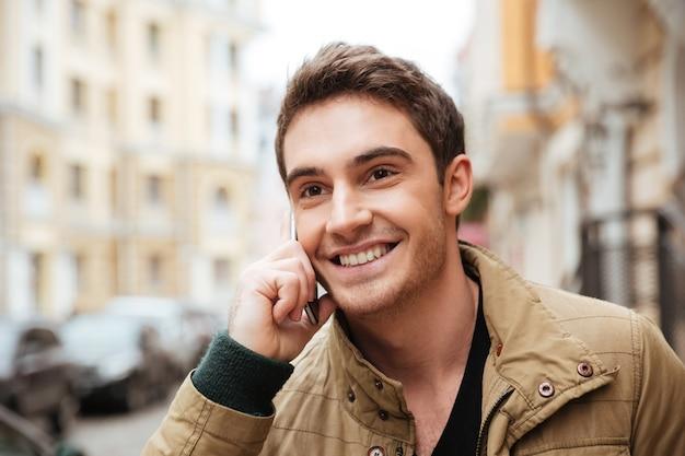 Imagen de hombre alegre caminando por la calle y mirando a un lado mientras habla por su teléfono.