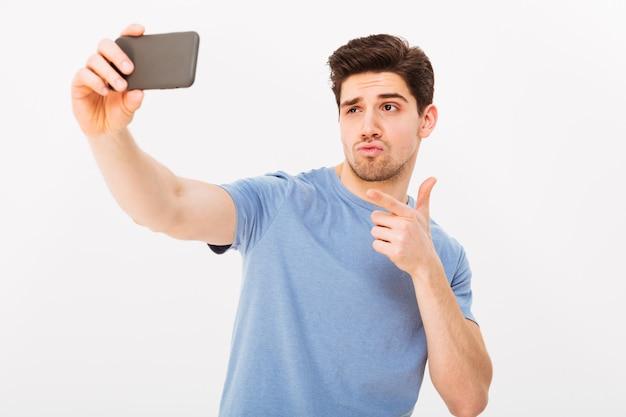 Imagen de hombre atractivo con cabello castaño y cerdas señalando con el dedo índice en la cámara mientras toma selfie en teléfono móvil negro, aislado sobre la pared blanca