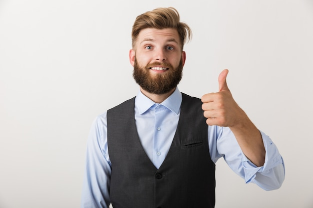 Imagen de un hombre barbudo joven feliz que se encuentra aislado sobre la pared blanca hace gesto de pulgar hacia arriba.