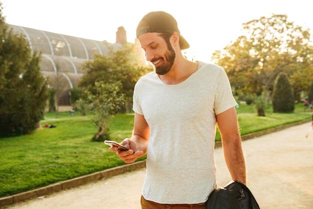 Imagen de hombre barbudo musculoso en ropa de calle sosteniendo y charlando en el teléfono móvil, mientras camina en el parque verde