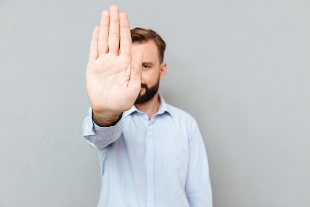 Imagen del hombre barbudo en ropa de negocios mostrando parada gesto
