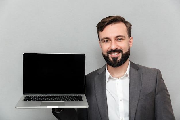 Imagen del hombre barbudo satisfecho que sostiene el cuaderno de plata que demuestra o que anuncia en la cámara, aislado sobre la pared gris