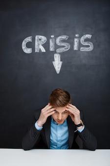 Imagen de hombre cansado sobre pizarra con inscripción de crisis