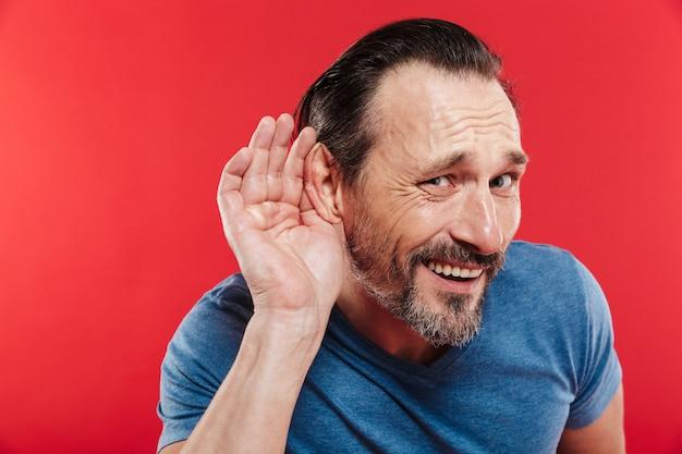 Imagen del hombre caucásico 30s en camiseta casual poniendo la mano a la oreja como escuchar o escuchar atentamente, aislado sobre fondo rojo.
