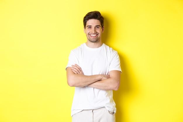 Imagen de hombre caucásico confiado sonriendo complacido, tomados de las manos cruzadas sobre el pecho y mirando satisfecho, de pie sobre fondo amarillo.