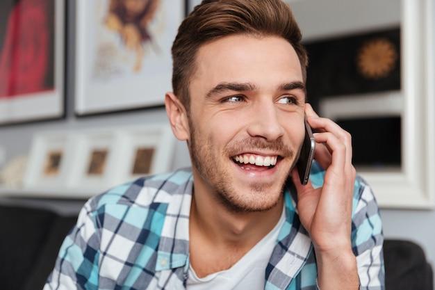 Imagen de hombre de cerdas riendo vestido con camisa en una jaula de impresión sentado en el sofá en casa y hablando por su teléfono.