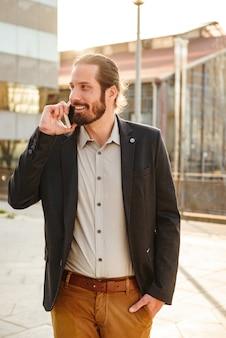 Imagen de hombre corporativo de contenido o gerente de oficina en traje sonriendo, mientras camina cerca del centro de negocios y habla por teléfono móvil