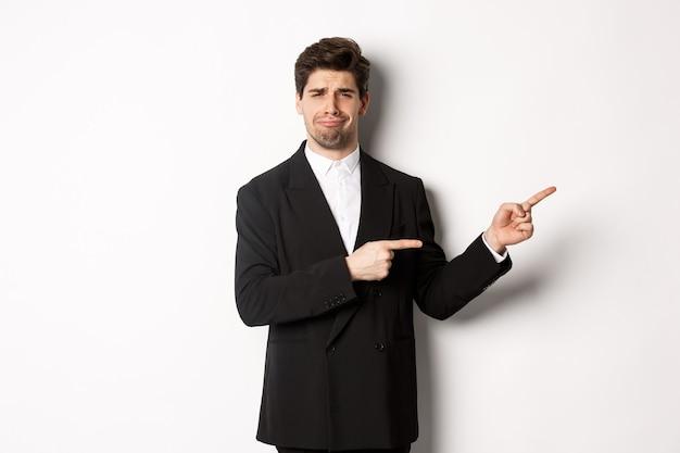Imagen de un hombre desanimado en traje de fiesta, llorando y quejándose, señalando con el dedo a algo decepcionante, de pie sobre fondo blanco.