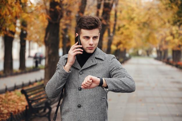 Imagen de hombre elegante que controla el tiempo con reloj en mano y hablando por teléfono móvil durante su caminata en el parque