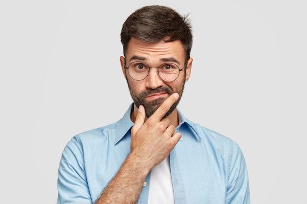Imagen de hombre europeo sin afeitar vacilante con barba espesa, sostiene la barbilla, frunce los labios con expresiones desorientadas