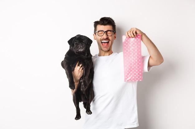Imagen de hombre feliz, dueño de la mascota, sosteniendo un lindo pug negro y una bolsa de caca de perro, de pie sobre fondo blanco.