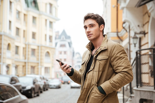 Imagen de un hombre guapo caminando en la calle y charlando con su teléfono al aire libre. mira a un lado.