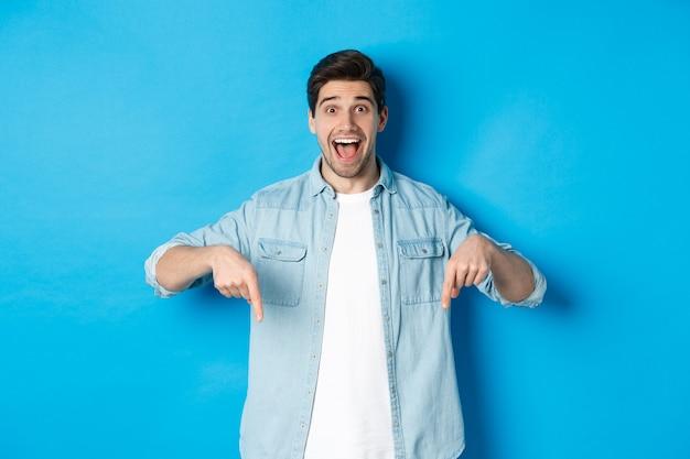 Imagen de un hombre guapo emocionado señalando con el dedo hacia abajo, haciendo un anuncio, de pie contra el fondo azul.