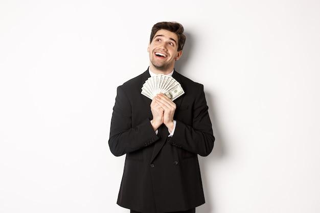 Imagen de hombre guapo de ensueño en traje negro, sosteniendo dinero y mirando en la esquina superior izquierda, pensando en ir de compras, de pie sobre fondo blanco.