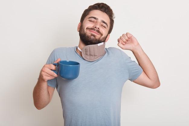 Imagen de hombre guapo tiene café de la mañana, todavía duerme, bosteza, de pie interior aislado sobre blanco