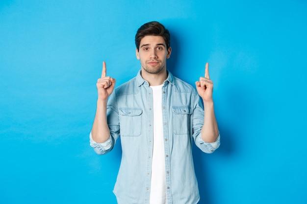 Imagen de un hombre guapo tranquilo que le muestra una oferta promocional, apuntando con el dedo hacia el espacio de la copia, de pie contra el fondo azul.