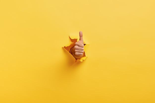 Imagen de hombre irreconocible hace gesto con el pulgar hacia arriba