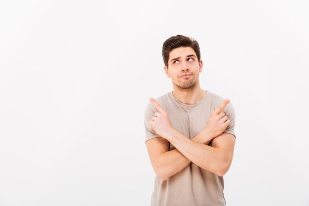 Imagen de hombre musculoso melancólico vistiendo camiseta beige gesticulando con los dedos a un lado con los brazos cruzados en copyspace, aislado sobre la pared blanca