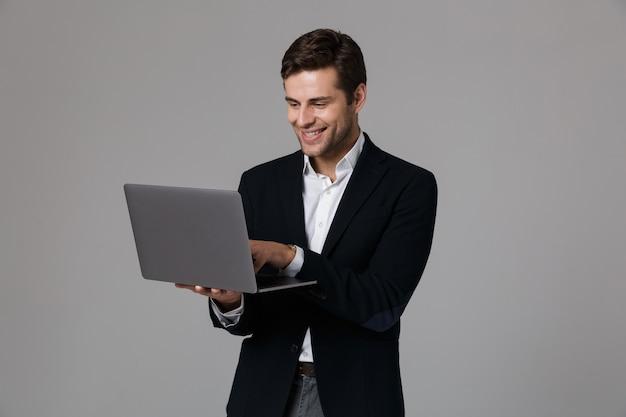 Imagen del hombre de negocios complacido de 30 años en traje regocijándose mientras usa un portátil, aislado sobre una pared gris
