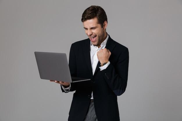 Imagen del hombre de negocios extático de 30 años en traje regocijándose mientras usa la computadora portátil, aislado sobre la pared gris