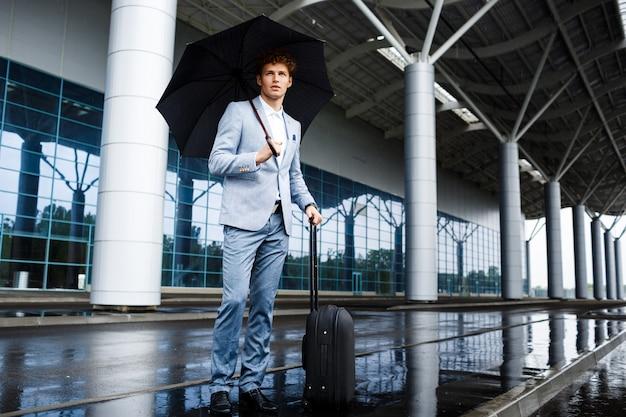 Imagen del hombre de negocios pelirrojo joven confiado que sostiene el paraguas negro y la maleta en lluvia en la terminal