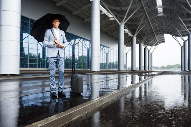 Imagen del hombre de negocios pelirrojo joven confidente que sostiene el paraguas negro en lluvia en el aeropuerto