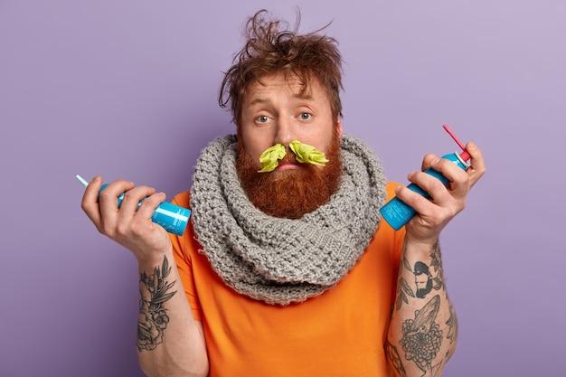 Imagen del hombre pelirrojo enfermo tiene moqueo, pañuelo en las fosas nasales, viste bufanda caliente tejida en el cuello