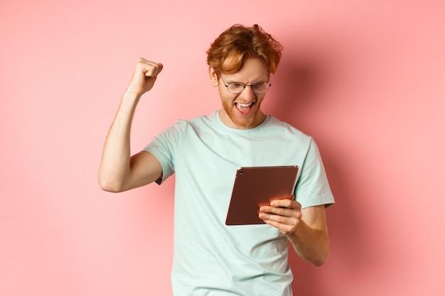 Imagen de hombre pelirrojo feliz triunfando, ganando online con tableta digital y regocijándose, de pie sobre fondo rosa.