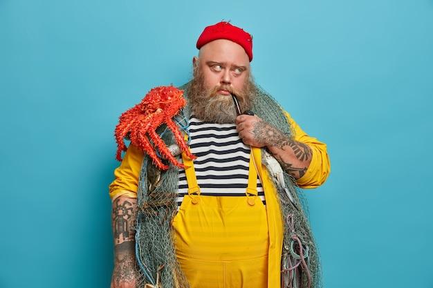 Imagen de hombre pensativo tiene ocupación marina, fuma pipa con expresión triste pensativa, posa con equipo de pesca, lleva pulpo, piensa en el próximo viaje o aventura por mar