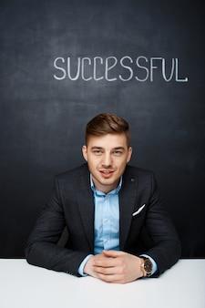 Imagen de un hombre que habla feliz sobre tablero negro con texto succ