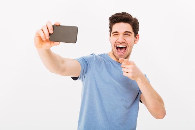 Imagen de hombre satisfecho con cabello castaño y cerdas sonriendo y señalando con el dedo a la cámara mientras toma selfie en teléfono móvil negro, aislado sobre la pared blanca
