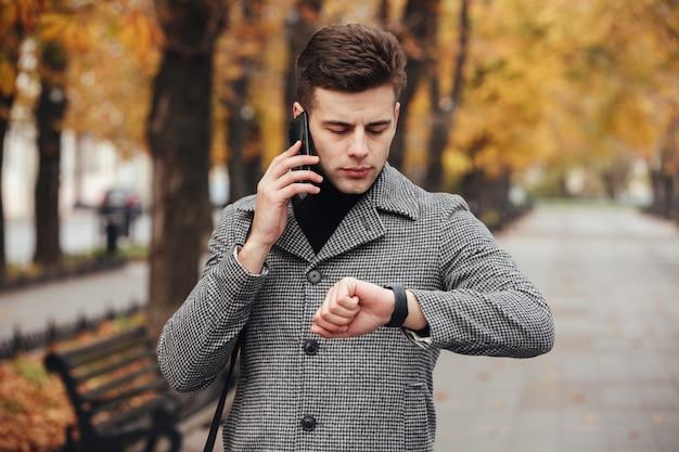 Imagen de un hombre serio hablando por teléfono móvil durante una reunión, verificando el tiempo con el reloj en la mano