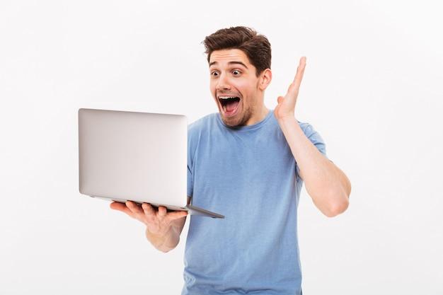 Imagen del hombre sonriente feliz con cerdas sosteniendo el cuaderno de plata y mirando emotinalmente en la pantalla de copyspace, aislado sobre la pared blanca
