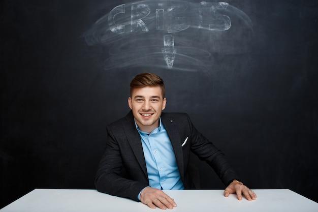 Imagen del hombre sonriente sobre pizarra con inscripción de crisis