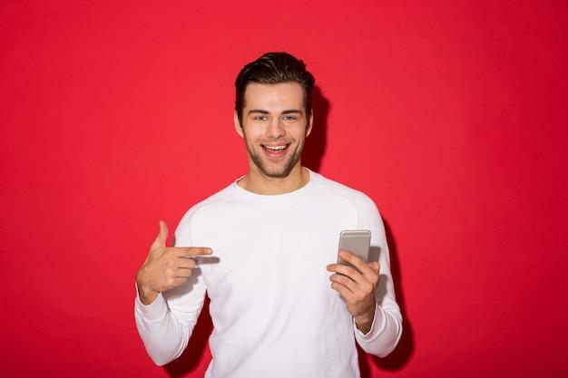 Imagen del hombre sonriente en suéter mirando mientras sostiene el teléfono inteligente y apuntando a él sobre la pared roja